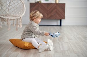 малко дете играе със самолетче на пода